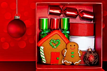 Gift Box Red Riempito Con Gingerbread Man e Gingerbread House, Red & Green Party Favors, Decorative Ribbon Red & White e Red, Verde & Gold Glitter Ornamenti di Natale su Red Textured Background con luci a LED
