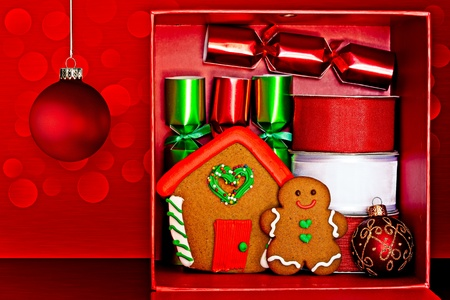 Red Gift Box Filled With Gingerbread Man and Gingerbread House, Red & Green Party Favors, Decorative Red & White Ribbon And Red, Green & Gold Glitter Christmas Ornaments Over Red Textured Background With LED Lights