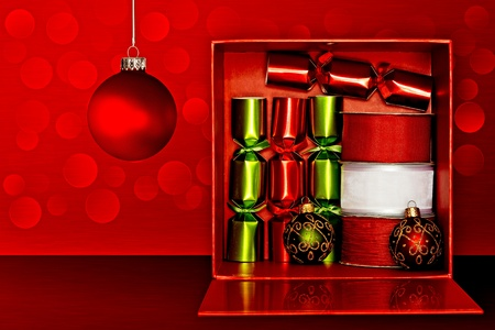 Red Gift Box Filled With Red & Green Party Favors, Decorative Red & White Ribbon And Red, Green & Gold Glitter Christmas Ornaments Over Red Textured Background With LED Lights Stock Photo - 11550440