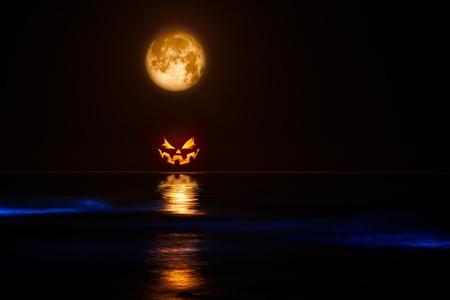 Pieno Harvest Moon e Jack-o-Lantern Mar Glowing con Sinister bio-luminescenza Waves Archivio Fotografico