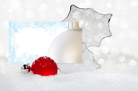 Elegant Silver and Red Christmas Ornament With Happy Holiday Text Greeting On White Card Nestled In White Snow With Glowing Lights Twinkling In Background Stock Photo - 11550405