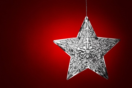 Silver Star Christmas Ornament Over Red Leather Background