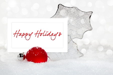 Elegant Silver and Red Christmas Ornament With Happy Holiday Text Greeting On White Card Nestled In White Snow With Glowing Lights Twinkling In Background