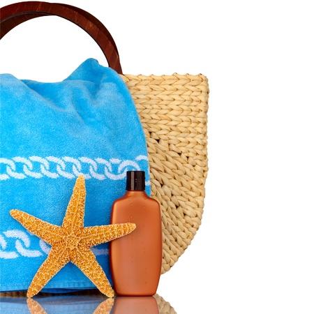 Straw Beach Bag, asciugamani blu, crema solare con gocce d'acqua e stelle marine Isolated On White