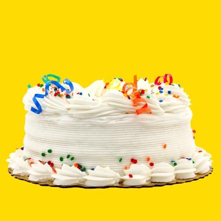 Heerlijke witte Vanille verjaardagstaart met Rood, Blauw, Groen, Geel en Oranje Decoraties ~~~V~~aux Geà ¯ soleerd Op Gele Achtergrond Stockfoto