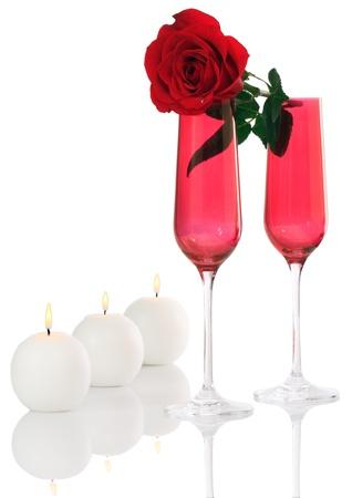 Isolato; romantiche Champagne Flutes rossi con Fresh Red Rose e candele bianche Archivio Fotografico