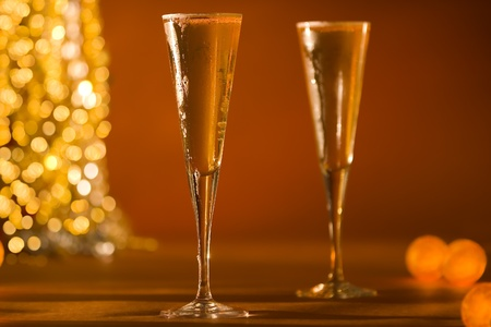 Close-Up of Fluted Champagne Glasss & Glowing Golden Lights photo