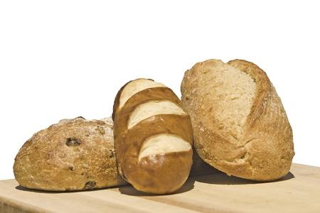 Appena sfornato intere pagnotte di pane di grano Riposo sul bordo di legno di taglio ~~~V~~aux isolato su sfondo bianco