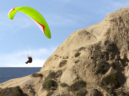 skydive: Paragliding Near Sand Cliffs Over The Blue California Pacific Ocean
