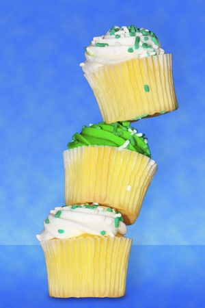 Three delicious vanilla cupcakes with green and white buttercream frosting stacked on top of each other Banco de Imagens