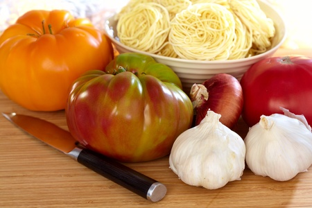 heirloom: Heirloom Tomatoes, Onion, Garlic, Pasta and Pairing Knife On Wood Cutting Board