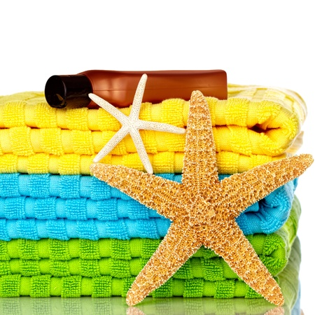Blue, Green and Yellow Beach Towels With Starfish And Sunscreen Isolated On White Background photo