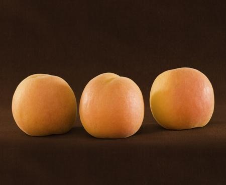 Three Ripe Organic Apricots On Brown Backround ~ Natural Light