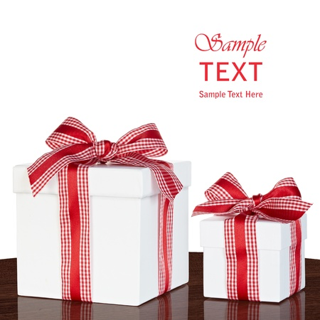 Presents In White Gift Box With Red & White Gingham Checked Ribbon Bow On Vintage Wood Table Isolated On White Background Archivio Fotografico