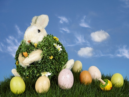 Festive Rabbit With Brown, Pink & Yellow Easter Eggs & Spinning Top, Sitting On Green Grass With Blue Sky And Clouds In Background