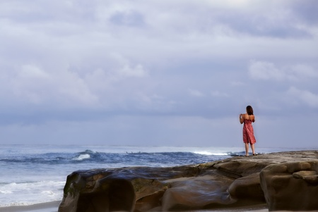 Woman in red summer sun dress standing on a rock bluff along the sea coast watching surfers and enjoying the tropical California waves of the Pacific ocean
