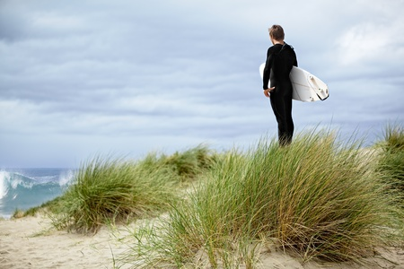 Male Surfer At The Beach, Standing In Green Sea Grass Sand Dunes On The Coast Of California ~ Boy On Vacation With Surf Board ~ Pacific Ocean Athletic Sport photo
