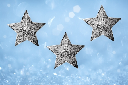 Three Metal Silver Star Christmas Ornaments Over Aqua Robins Egg Blue and White Snow Background