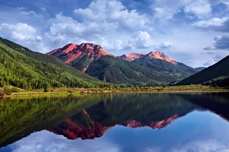 skyway: Colorado San Juan Skyway, Red Iron Peaks Reflecting In A Crystal Clear High Mountain Lake With Conifer Pines and Aspens, USA  Stock Photo