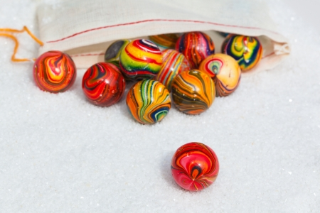 Collection Of Hand Cut & Ground Banded Vintage Agate Marbles ~ Retro Quartz Stone Speres Sitting On White Sand With Game Pouch Toy Bag ~ Green, Red, Orange, Yellow, Blue Swirls Archivio Fotografico