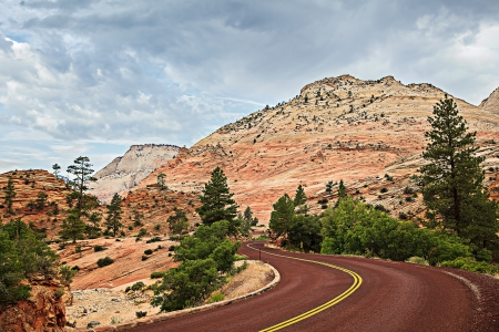 Curved Red Rock Asphalt Road Running Through The Landscape Of Sandstone Rock Mountain Formations In Zion National Park In Utah, USA  photo