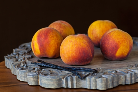 Group OF Fresh Ripe Peaches With Vannilla Beans On Wooden Decorative Platter Dark Chocolate Brown Wallpaper Background Archivio Fotografico