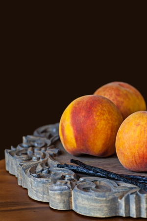 Group OF Fresh Ripe Peaches With Vannilla Beans On Wooden Decorative Platter Dark Chocolate Brown Background