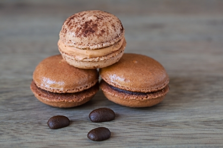 French Chocolate   Coffee Macaroons And Coffee Beans, Tasty Gormet Meringue Cookie Sandwich Cake on Vintage Wood Background  photo