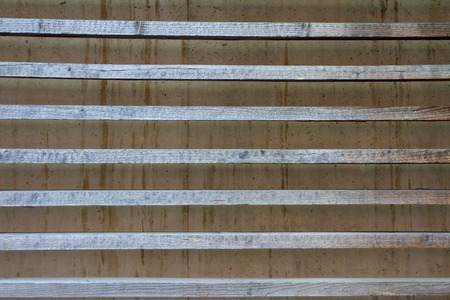 struts: Concrete wall with intent from the grayed wood struts Stock Photo