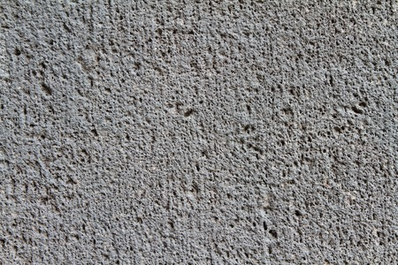 Close up of a coarse, dark gray concrete wall