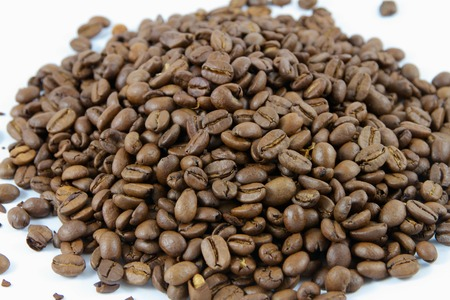 Close up of a pile of coffee beans on a white background