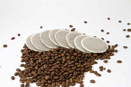 Coffeepads a pile of coffee beans Standard-Bild