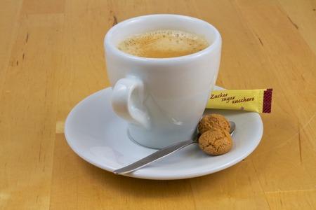 sachets: Vista de una taza de caf� con sobres de az�car y galletas en un fondo blanco Foto de archivo