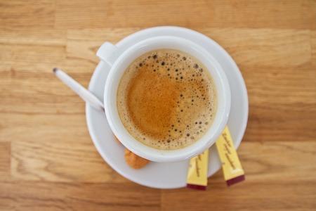 sachets: Vista de una taza de caf� con sobres de az�car y galletas sobre un fondo blanco Foto de archivo