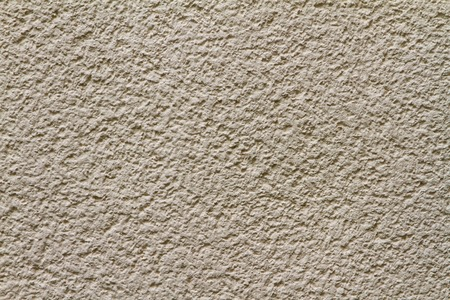 Detalaufname of bright-yellow plaster wall Standard-Bild