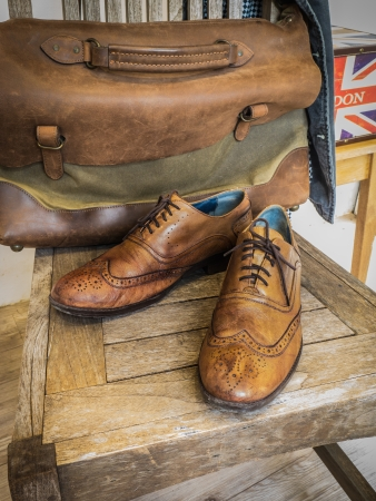 Vintage male clothing   Brown wingtip leather shoes,  Vintage leather messenger bag ,Vintage gray jacket, and Fedora hat  Stock Photo