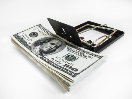 Money in a mousetrap on a white background photo