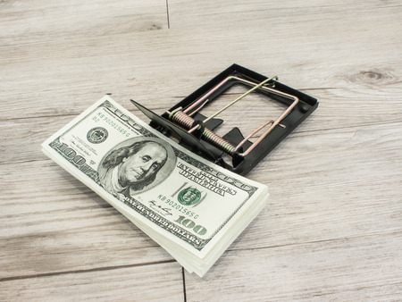 Money in a mousetrap on a wood background