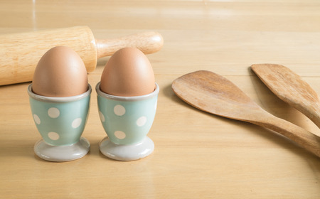 Two fresh brown eggs in blue polka dot egg cups and baking utensils on the wood table photo