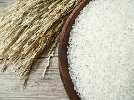 Close up white rice on the wooden plate and rice plant ,  uncooked raw cereals photo