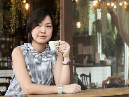 Junge asiatische Frau vor Ort im Café tragen eine Tasse Tee Standard-Bild - 37848662