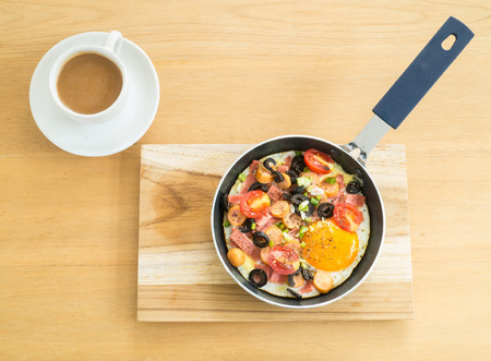 Fried egg with sausage ,tomatoes and olives in a pan on wooden tray and white cup of  hot coffee on wooden table for breakfast photo