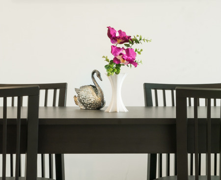 Vase of flower and silver carve statue swan on a table.Decorative interior dining room photo