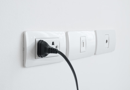 wall socket: Close up of electronic power plug plugged in a wall socket.