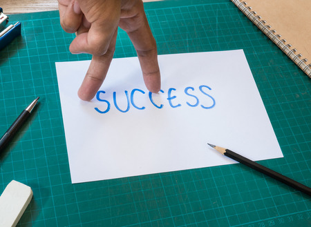 Forefinger and middle finger look like walking action on success text paper. photo