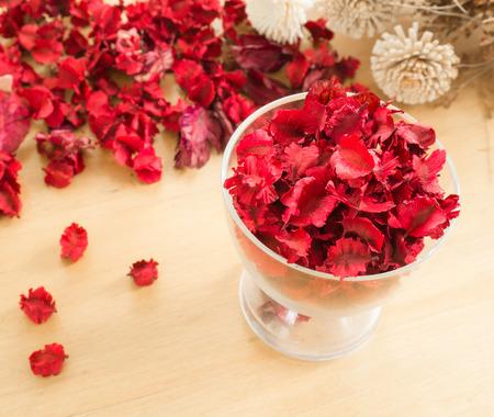 flores secas: Rojo Flores secas y hojas de vidrio sobre un fondo placas de madera Foto de archivo