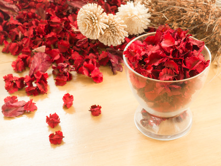 dried flowers: Red Dried flowers and leaf in glass on a wooden  plates background