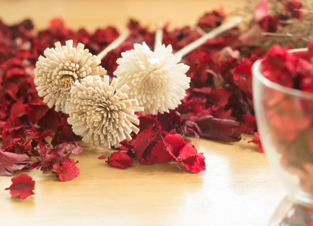 dried flowers: Brown Dried flowers in the red leaf on a wooden plates background