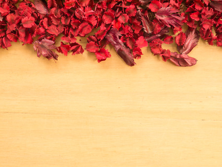 dried flowers: Frame of Red Dried flowers and leaf on a wooden plates background ( Space and composition for text) Stock Photo