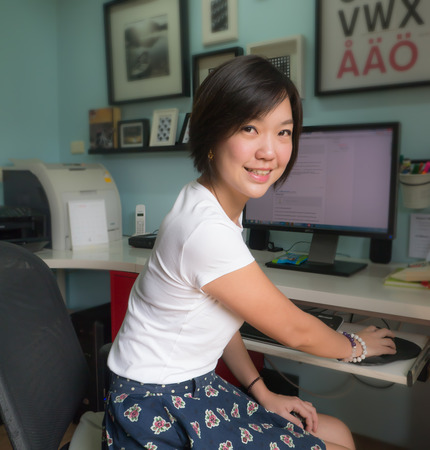 Portrait of Asian woman with computer in home office smile and look at camera